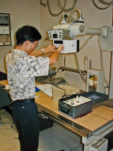 Inspector conducting a routine test on an x-ray unit.
