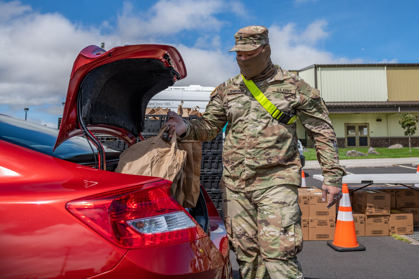 a man places supplies into a car trunk Hawaii Public Housing Authority - Hawaii Department of Health and Hawaii Air National Guard