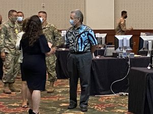 a man standing among National Guard, doctors and computers