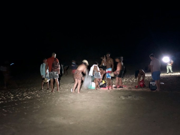 several beach goers cleaning up party litter at night