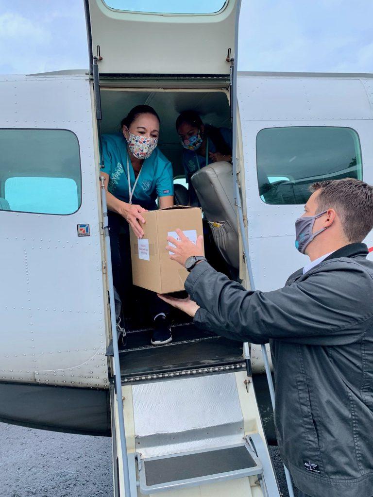 a woman and man handing off a fragile cardboard box through an airplane door