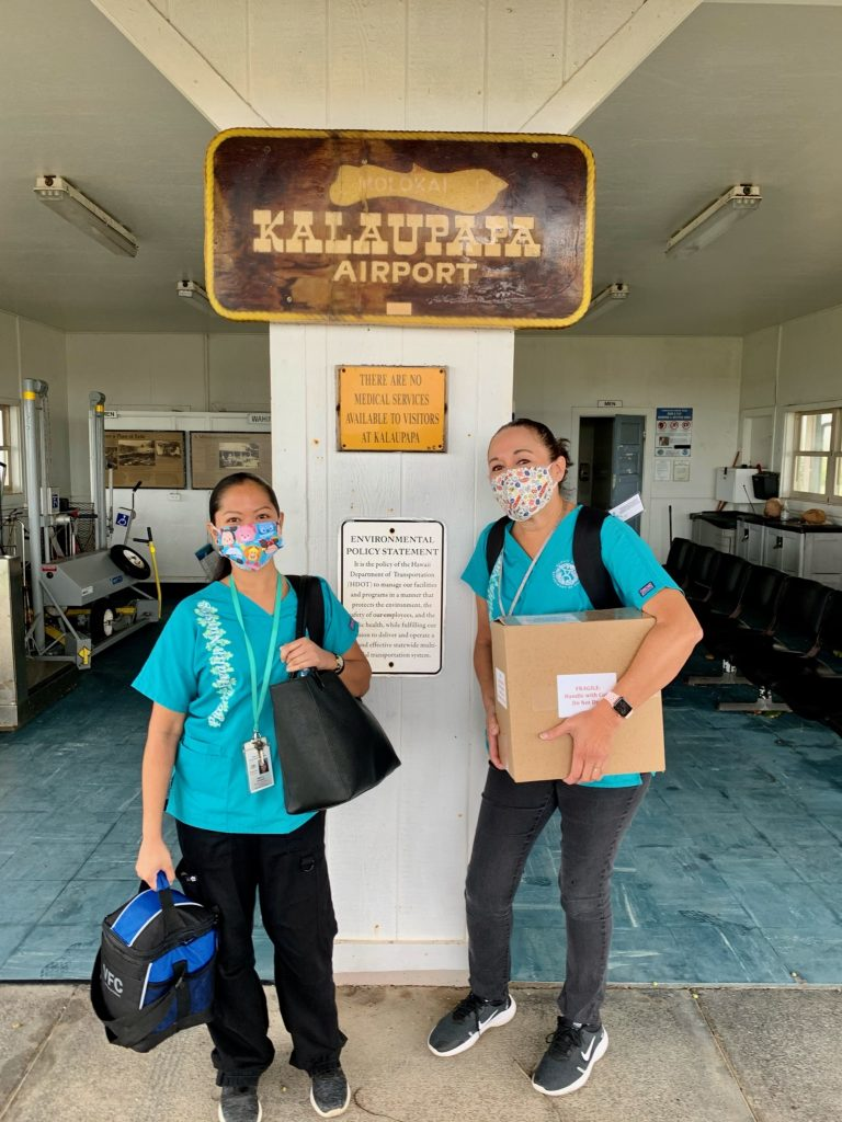 two women wear masks and carry gear at Kalaupapa airport