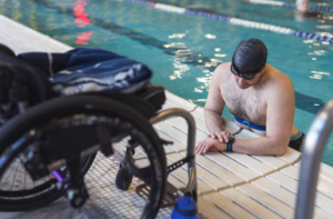 Swimmer getting out of pool next to his wheelchair