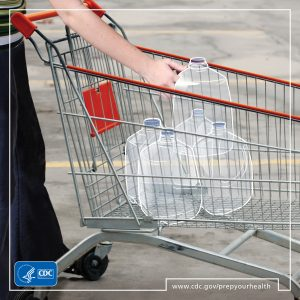 woman with shopping cart gets water for her emergency kit