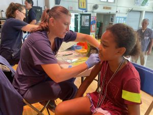 elementary student receives a flu vaccine from a public health nurse