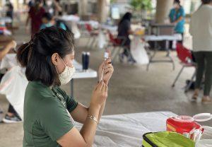 A public health nurse prepares to give a COVID-19 vaccine in a drill